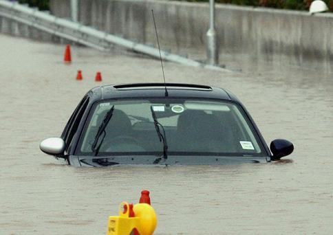 A motorist's car is abandoned after severe floods in the Westlink area of Belfast.