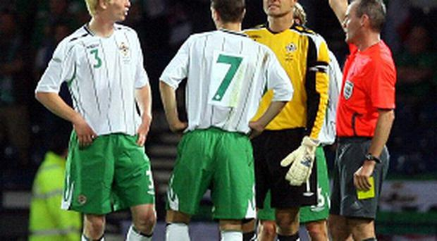 Ryan McGivern can't believe it as he is sent off on his debut against Scotland
