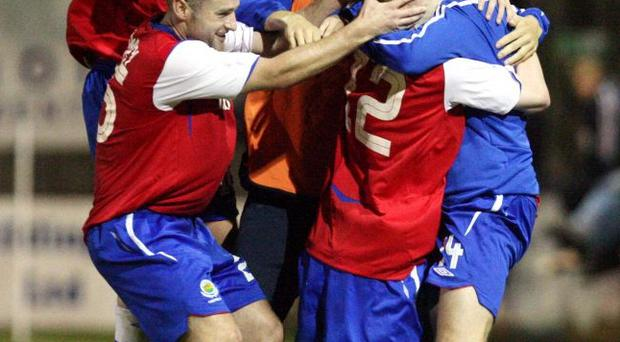 Goalscorer Billy Joe Burns is mobbed by his Linfield team-mates after his injury time strike seals a point for the defending champions