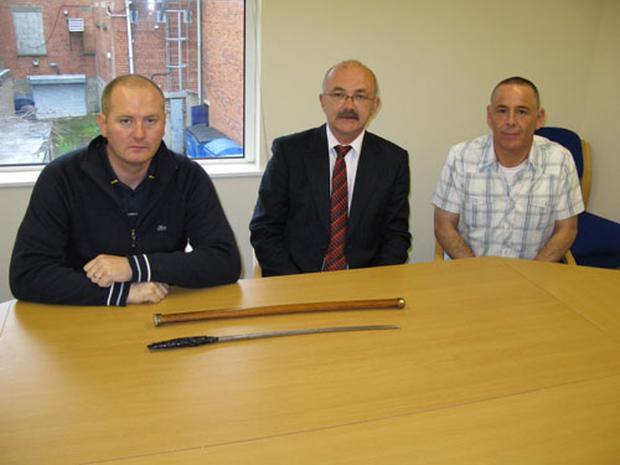 (L-r) Stephen Magennis, Brian McCrory and Colin Patterson of the Finaghy Crossroads Group with the machete that was found in the Woodlands Playing Fields over the weekend