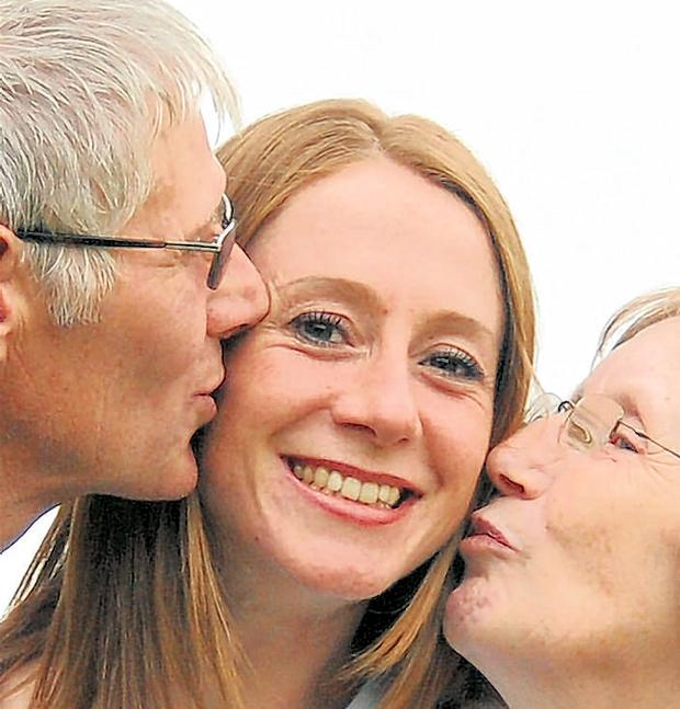 A welcome home kiss for silver medallist Wendy from her parents May and Philip McLean