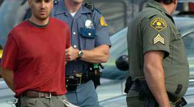 Washington State Troopers and a Skagit County Sheriff's Deputy lead shooting suspect, Isaac Zamora, 28, to the county jail, Tuesday Sept. 2, 2008 in Mount Vernon, Wash., after he led authorities on a high speed chase from Alger, Wash.