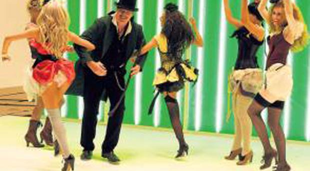 Patrick Bergin coverts with scantily clad dancers in the video