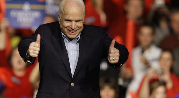 John McCain gives a thumbs-up to supporters before a speech at a Republican rally in Davenport, Iowa, at the weekend