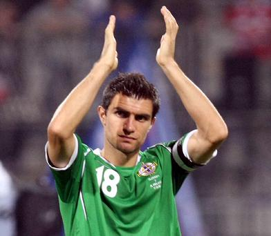 Aaron Hughes applauds the Northern Ireland fans after the 2-0 defeat at the hands of Slovenia