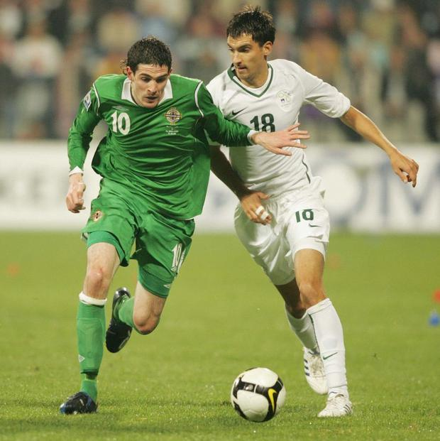 Northern Ireland's Kyle Lafferty tries to take the ball away from Slovenia's Ilic Branko