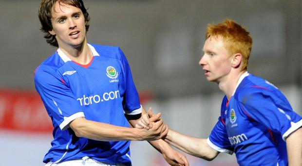 Linfield's Paul Munster (left) celebrates scoring against Cliftonville