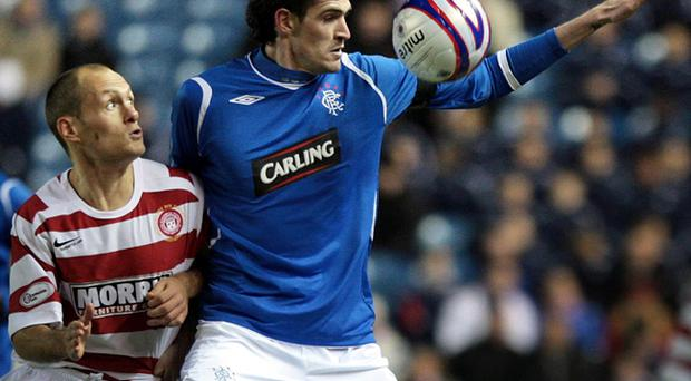 Kyle Lafferty holds off Hamilton Academical's Alex Neil during the CIS Insurance Cup match at Ibrox Stadium