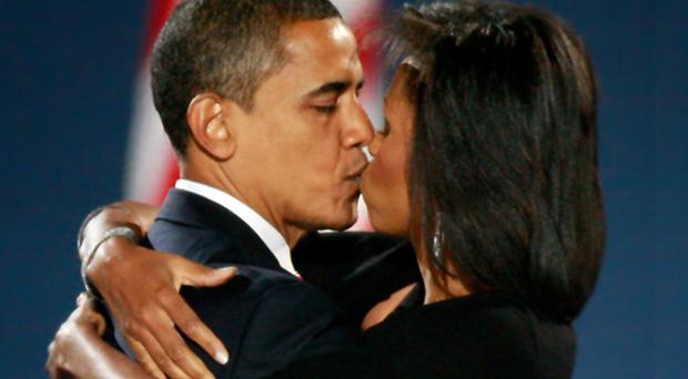 US President elect Barack Obama kisses his wife Michelle after Obama gave his victory speech during an election night gathering in Grant Park on November 4, 2008 in Chicago, Illinois.