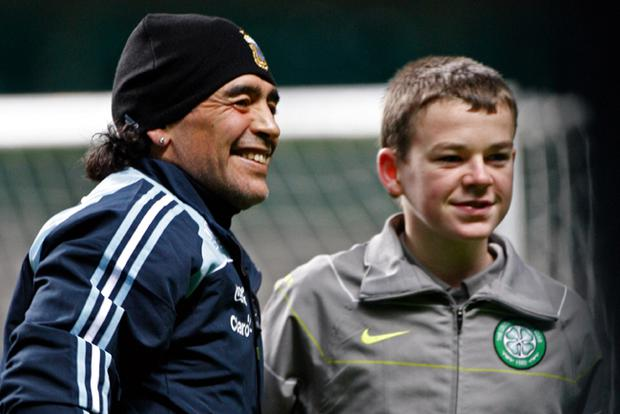 Maradona poses with 13-year-old Adam Brown at Celtic Park. Adam found the St Christopher medallion lost by Argentine midfielder Fernando Gago during last night's training session