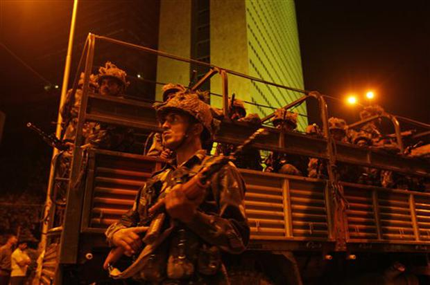 Indian army soldiers take positions near the Oberoi hotel in Mumbai, India, Thursday, Nov. 27, 2008. Black-clad Indian commandoes raided two luxury hotels to try to free hostages Thursday, and explosions and gunshots shook India's financial capital a day after suspected Muslim militants killed people. Backdrop is of the Air India building. (AP Photo/Gurinder Osan)