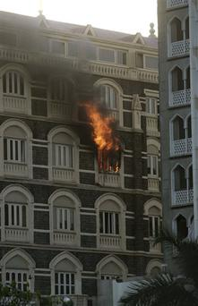 Flames come from a room of the Taj Mahal hotel in Mumbai, India, Thursday, Nov. 27, 2008. Black-clad Indian commandoes raided two luxury hotels to try to free hostages Thursday, and explosions and gunshots shook India's financial capital a day after suspected Muslim militants killed people. (AP Photo/Gurinder Osan)