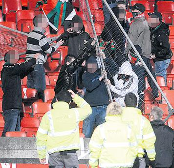 Glentoran fans are restrained by stewards at Windsor Park in Belfast yesterday as fans of the east Belfast club clashed with Linfield supporters. Some fans broke through the exclusion barrier separating rival followers