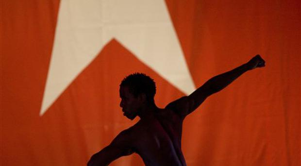 A dancer performs during the 50th anniversary celebration of the Cuban Revolution at the main plaza in Santiago, Cuba Thursday Jan. 1, 2009. Fifty years after triumphant armed rebels took power, Cuba celebrated the revolution's anniversary Thursday with toned-down festivities following a trio of devastating hurricanes and under the enduring public absence of an ailing Fidel Castro. (AP Photo/Dario Lopez-Mills)