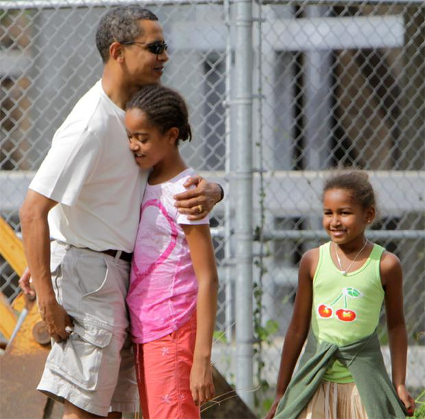 Barack Obama pictured with his daughters Malia (centre) and Sasha