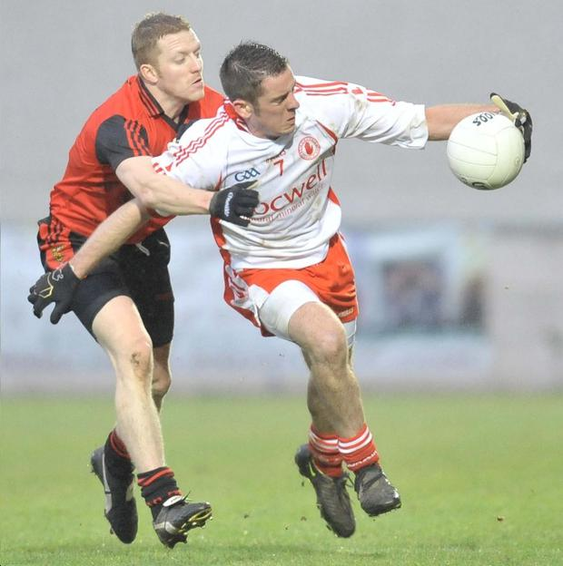 Tyrone's Phillip Jordan shakes off the challenge from Down's John Fagan