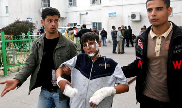 A Palestinian boy is helped as he leaves the Kamal Adwan hospital after being treated for burns following Israeli strikes on January 11, 2009 in Beit Lahia northern of Gaza Strip
