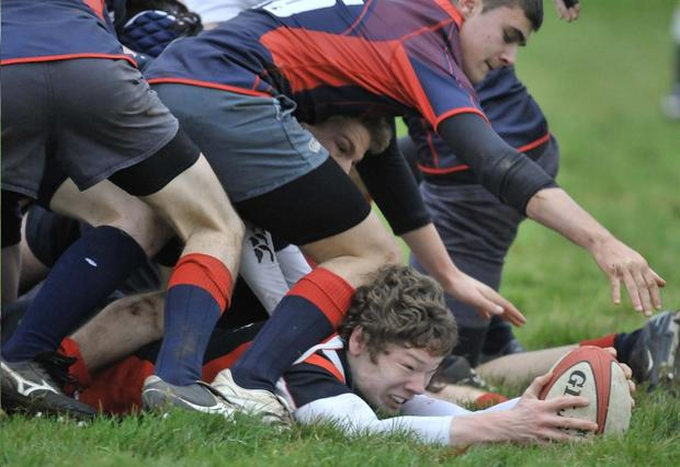 Wellington's Johnny McCormick does well to drive over and score a try against Lurgan College