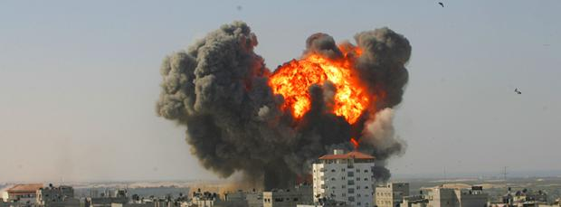 Flames and debris rise following an Israeli air strike on January 13, 2009 in Rafah, Gaza Strip