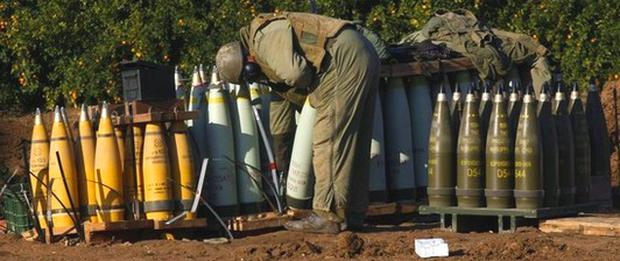 An Israeli soldier stands infront of pale blue 155mm rounds marked M825A1. According to Jane's Missiles and Rockets the M825A1 rounds are US-made white phosphorus munitions.