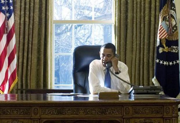 US President Barack Obama talks on the phone in the Oval Office of the White House in his first complete day as Commander-in-Chief