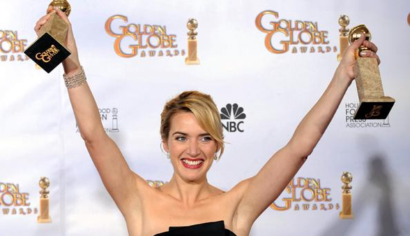 Kate Winslet poses with Golden Globe awards for best actress drama for Revolutionary Road and supporting actress for The Reader
