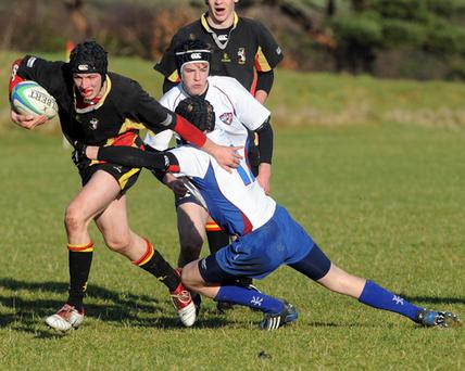 Foyle and Londonderry College against Dalriada at City of Derry Rugby ground. Foyle's A Patteson tries to break through a tackle from Dalriada's J McMullan.