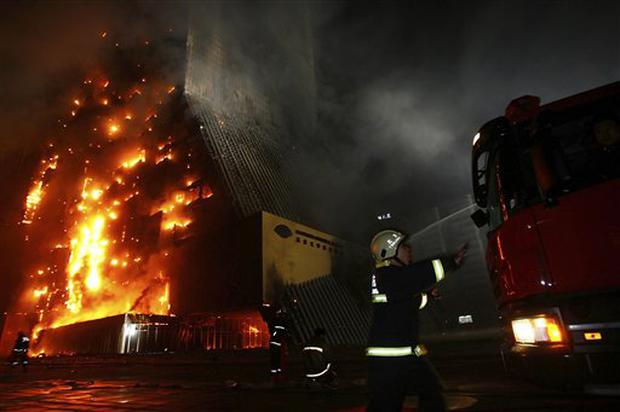 Firefighters prepare to put out the fire at the unfinished Mandarin Hotel in Beijing, China, Monday, Feb. 9, 2009. One fireman was killed fighting a blaze that destroyed the 44-story luxury hotel being constructed as part of Beijing's frenetic Olympic makeover and next door to the landmark China Central Television (CCTV) headquarters. (AP Photo/Color China Photo) ** CHINA OUT **