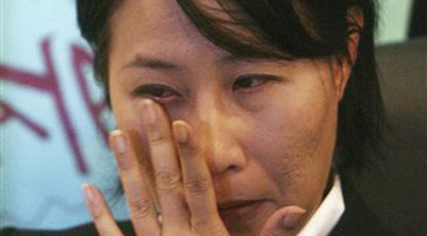 Elizabeth Wong, a prominent Malaysian opposition legislator, wipes tears as she hold a news conference at the National Justice party's office in Petaling Jaya, outside Kuala Lumpur, Malaysia, Tuesday, Feb .17, 2009. Elizabeth Wong resigned Tuesday after photographs of her sleeping naked were circulated to the public by cell phone, an embarrassing disclosure that she slammed as a plot to discredit her party. (AP Photo)