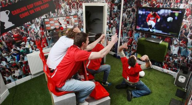Phil Spark (above, back row, right) brought football home to his front room with the installation of a turnstile, fake turf, stadium seats and a pie heater borrowed from a local chippy