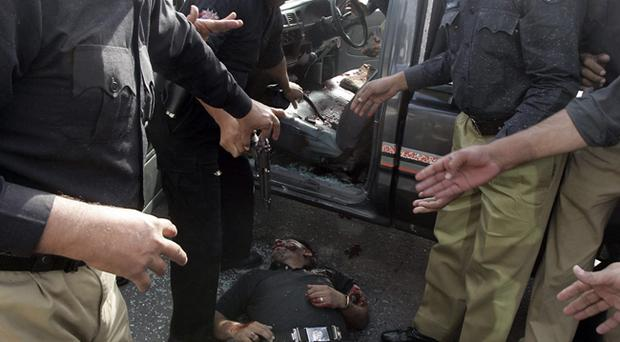 Pakistani police officers gather around the dead body of a police commando at the shooting site in Lahore, Pakistan.