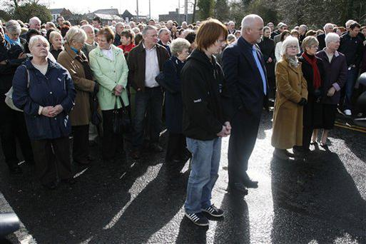 Local parish members hold a prayer service at Massereene army barracks in Antrim, west of Belfast, Northern Ireland Sunday, March, 8, 2009 after two British soldiers were shot to death and four other people wounded in a drive-by ambush that politicians blamed on IRA dissidents. Suspected IRA dissidents who opened fire on British soldiers and pizza delivery men outside an army base shot their victims again as they lay wounded on the ground, police said Sunday. Two soldiers died and four other people, including two men delivering pizzas, remained hospitalized with serious wounds following Saturday night's attack at the entrance to Massereene army barracks in Antrim, west of Belfast. (AP Photo/Peter Morrison) (AP Photo/Peter Morrison)