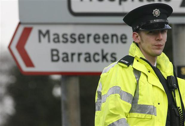 A police officer patrols outside the Massereene army barracks in Antrim, west of Belfast, Northern Ireland, Sunday, March, 8, 2009 after two British soldiers were shot to death and four other people wounded in a drive-by ambush Saturday that politicians blamed on IRA dissidents. Suspected IRA dissidents who opened fire on British soldiers and pizza delivery men outside an army base shot their victims again as they lay wounded on the ground, police said Sunday. Two soldiers died and four other people, including two men delivering pizzas, remained hospitalized with serious wounds following Saturday night's attack at the entrance to Massereene army barracks in Antrim, west of Belfast. (AP Photo/Peter Morrison)