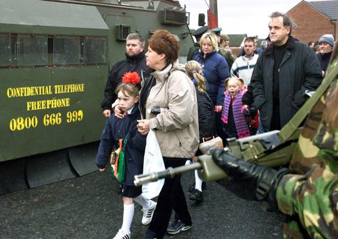 Riot police and British soldiers escort Catholic schoolgirls and their parents through the Holy Cross protest in 2001