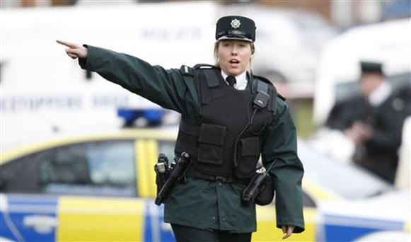 Police Service of Northern Ireland officers take up position near Lismore Manor, Craigavon, Northern Ireland, Tuesday, March 10, 2009. A large security presence has begun after a Police Service of Northern Ireland officer was shot dead by suspected Irish Republican terrorists. (AP Photo/Peter Morrison)