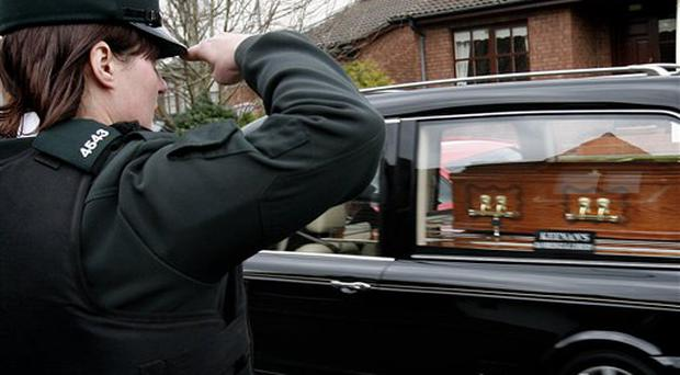 A Police Service of Northern Ireland officer salutes the coffin of Stephen Paul Carroll as his remains arrive back at his home in Banbridge, Northern Ireland, Wednesday, March, 11, 2009. The PSNI officer was gunned down late Monday by Irish Republican terrorists. Several thousand Catholics and Protestants united in a silent protest Wednesday against the Irish Republican Army dissidents who have put Northern Ireland on edge _ and its peace in doubt _ with deadly attacks that have left three dead since the weekend. (AP Photo/Peter Morrison)