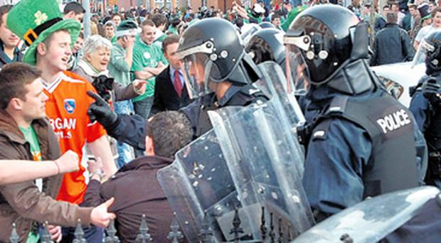 Scenes of chaos: St Patrick's Day revellers and police in riot gear in the Holy Land area of south Belfast