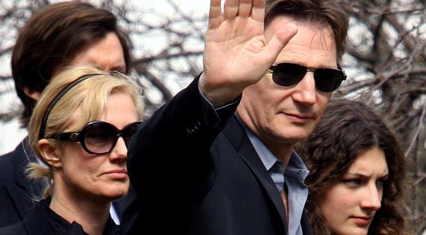 Liam Neeson waves to journalists as he arrives with family and friends to the funeral of his wife Natasha, March 22, 2009