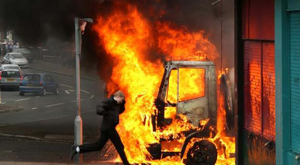 A burning van outside Holy Cross church in north Belfast