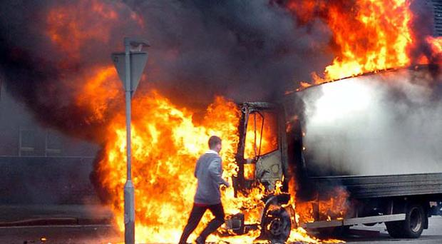 A schoolboy darts past a blazing lorry in the Ardoyne area of Belfast in scenes Northern Ireland thought it had finally consigned to the history books.