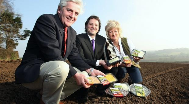 Burying the competition: Ulster Bank's Richard Ennis, centre, marked the company's awards victory with Mash Direct owners, Martin and Tracy Hamilton, at their farm in Comber