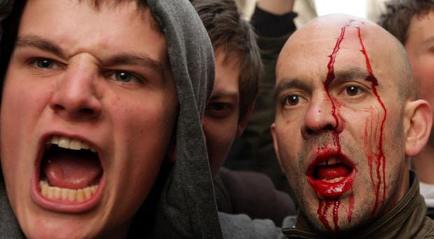 Bloodied protesters shout at police near to the Bank of England as anti capitalist and climate change activists demonstrate in the City of London on April 1, 2009 in London, England