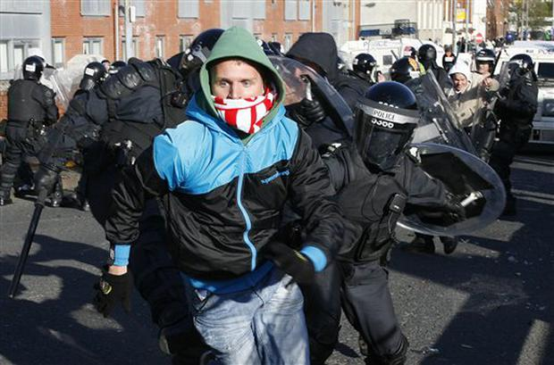 A Polish fan clashes with officers as rioting breaks out before their soccer match with Northern Ireland during their World Cup qualifying soccer match at Windsor Park, Belfast, Northern Ireland, Saturday, March 28, 2009. (AP Photo/Peter Morrison)