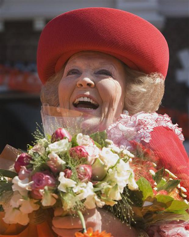 Queen Beatrix of the Netherlands greets wellwishers, shortly before a car ploughed into the crowd, during festivities marking Queen's Day in Apeldoorn, Netherlands, Thursday, April 30, 2009. Dutch authorities say a speeding car that raced toward an open bus carrying Dutch Queen Beatrix and her family during a holiday parade has killed four people and injured 13 others. Prosecutors said the incident was deliberate, but not an act of terrorism. The small black car was heading at high speed toward the royal bus and passed within a few meters of it before plowing into a stone monument. Police declined to identify the driver beyond saying he was a white Dutch male, aged 38, who had no police record or history of mental illness. (AP Photo/Robin Utrecht, Pool)