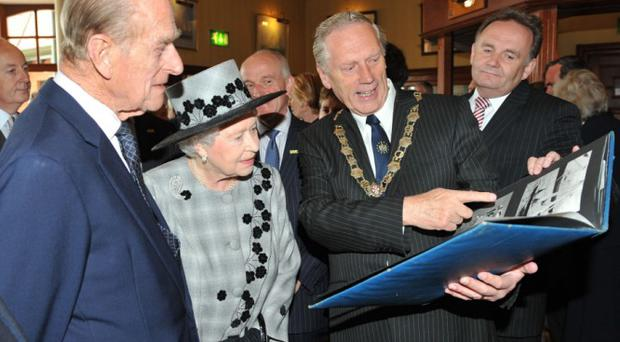 Her Majesty the Queen and Prince Philip are shown pictures from a previous visit by the Queen in the 1960's by Mayor of North Down Alderman Leslie Cree at the Royal Ulster Yacht Club in Bangor this afternoon (Thursday) as part of her visit to Northern Ireland.Photo by Aaron McCracken/Harrisons