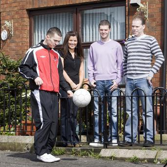 Martin Donnelly shows off his ball skills in front of the family home in north Belfast, watching by some of his biggest fans — dad Gerry, sister Shauna and brother Gerry