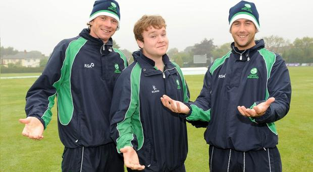 Peter Johnston, Ireland's video analysis technician, Paul Stirling and Phil Eaglestone smile through the rain at a sodden Clontarf