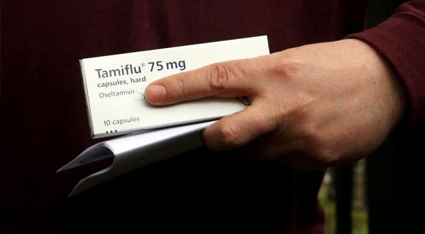A man holds a box of the anti-viral drug, Tamiflu