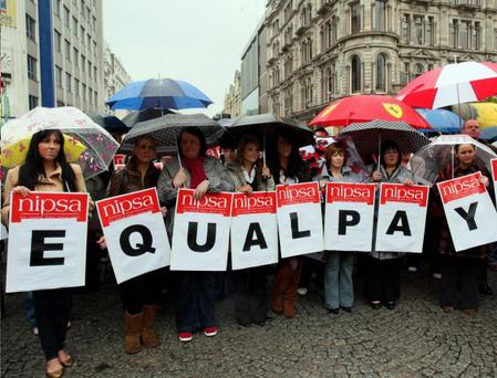 Several hundred protesters brave the rain to demonstrate against the hold up in implementing back pay deal