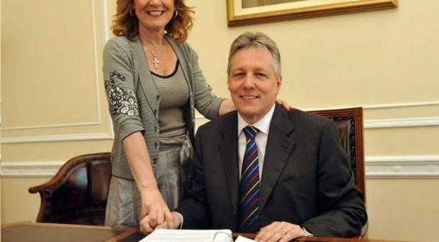 Northern Ireland's First Minister Peter Robinson with his wife Iris at his desk at Parliament Buildings, Stormont, Northern Ireland